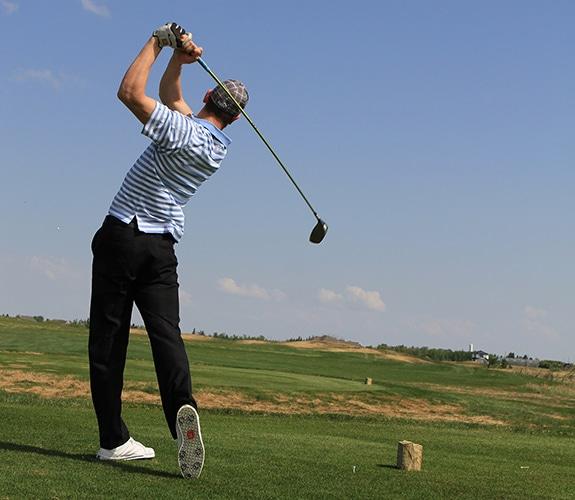 Male golfer follow through swing